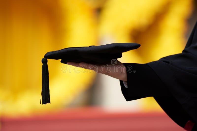 Eine Hand, die graduierte Kappe auf gelbem Hintergrund hält stockbild