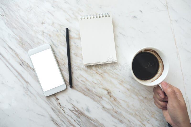 Eine Hand, die Kaffeetasse mit einem weißen Handy mit leerem Tischplattenschirm und leerem Notizbuch auf Tabelle hält stockfoto