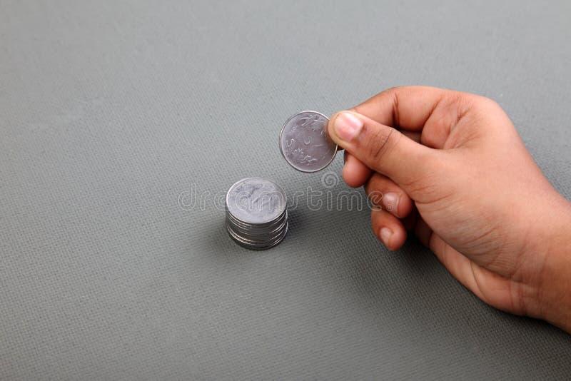 Eine Hand, die Münzen der indischen Rupie sammelt stockbild