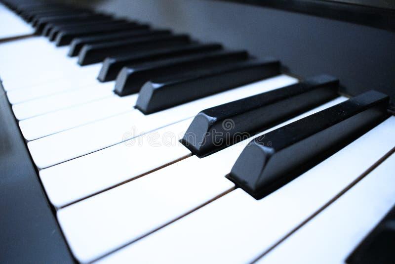 Eine Hand, die mit Klaviertastaturhintergrund mit selektivem Fokus spielt Normale Farbe getontes Bild stockfotos