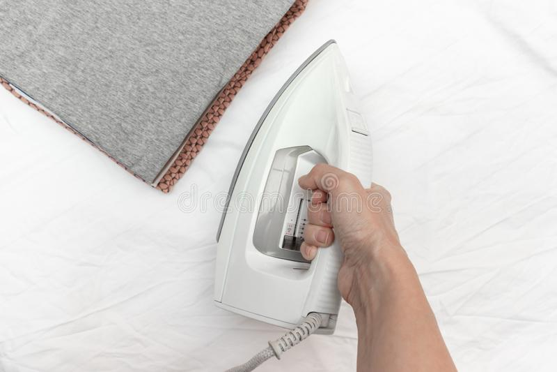Eine Hand, die modernes elektrisches weißes Eisen bereit, einen Stapel Kleidung zu bügeln - Bügeln, Wäscherei und Hausarbeitkonze stockfotos