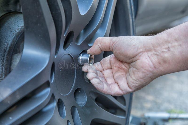 Eine Hand, die eine Schraube zum Rad eines Autos befestigt lizenzfreie stockfotografie