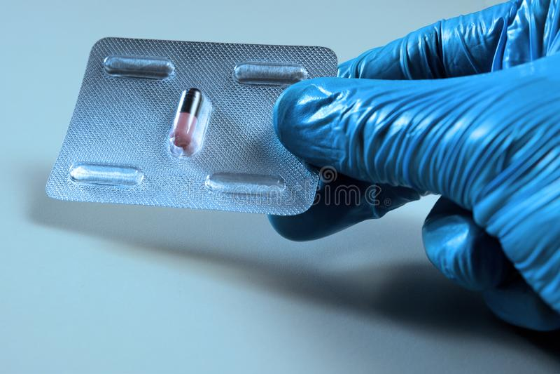 Eine Hand in einem blauen Laborhandschuh hält eine Blase mit einer Pille Medizinisches Konzept, Gesundheit und Geschäft, Krankhei lizenzfreies stockfoto
