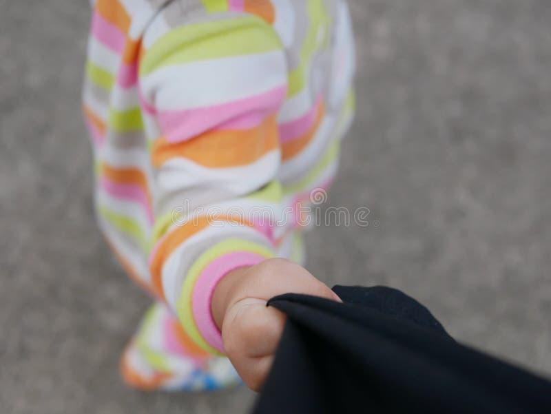 Eine Hand eines kleinen Babys, das ihre Vatihosen zieht lizenzfreie stockbilder