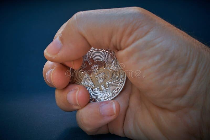 Eine Hand ergreift eine bitcoin Münze Die Münze glänzt und reflektiert Licht Der Hintergrund ist dunkel und abstrakt Die BTC-Währ stockbilder