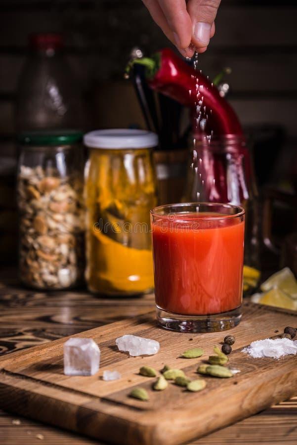 Eine Hand gießt Salz in ein Glas Tomatensaft auf einem hölzernen Brett mit Gewürzen, Salz und Kürbiskerne lizenzfreie stockfotos