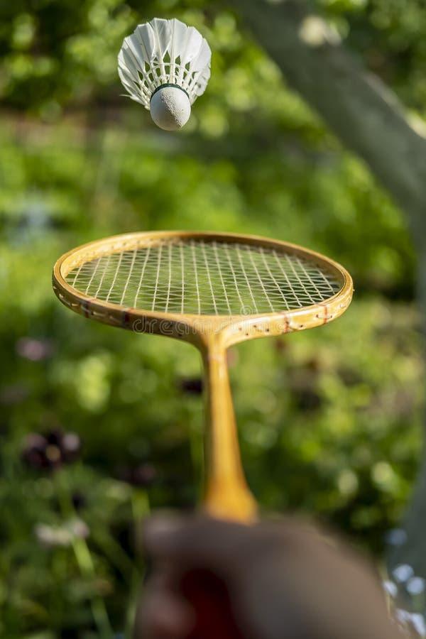 Eine Hand hält einen Federballschläger und wirft einen Federball, auf einem unscharfen grünen Hintergrund, an einem Sommertag lizenzfreies stockfoto