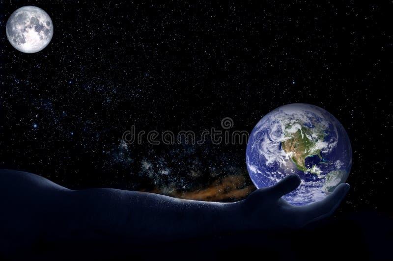 Eine Hand hält eine Kugel auf einem Hintergrund von Sternen und von Mond stockbild