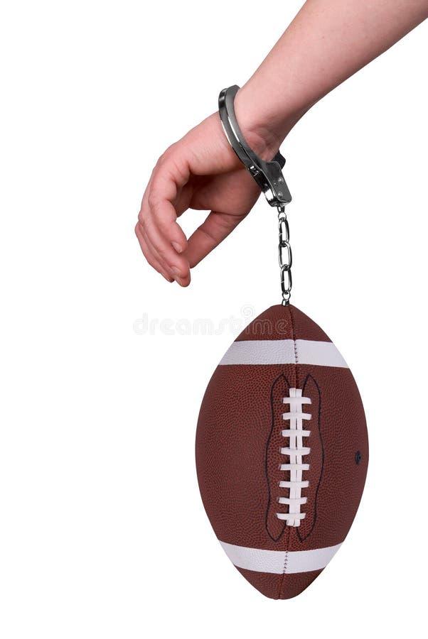 Eine Hand mit Handschellen gefesselt zu einem Fußball stockbild
