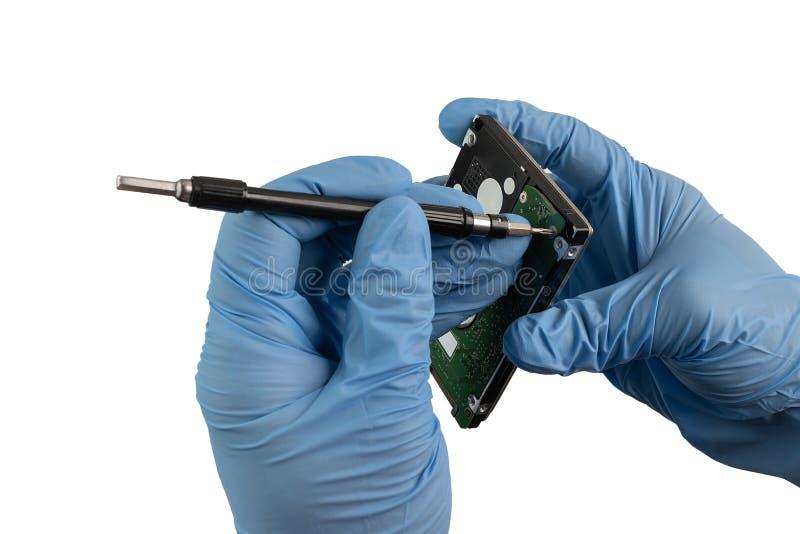 Eine Hand mit Handschuh schraubt eine Festplatte ab stockfotografie