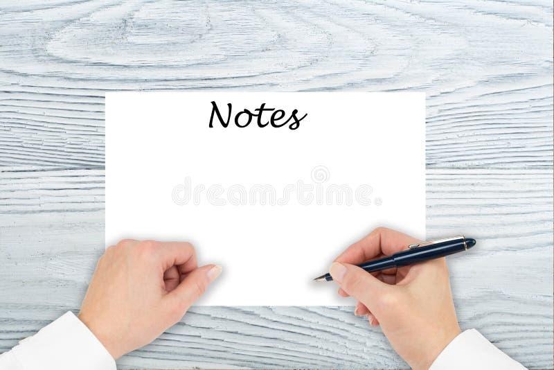 Eine Hand schreibt auf ein Papier auf einem Holztisch Machen Sie Wunschzettel, Anmerkungen, Pl?ne, schreiben Sie, abgehobener Bet lizenzfreies stockfoto