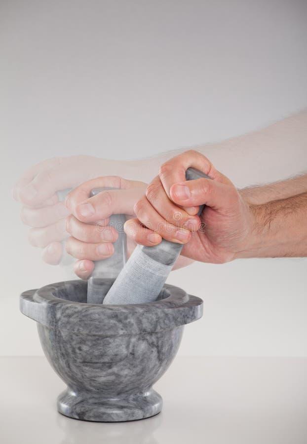 Eine Hand unter Verwendung eines Mörsers und einer Stampfe lizenzfreie stockbilder