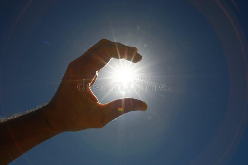 Eine Hand, welche an die Sun-Sterne fängt stockbild