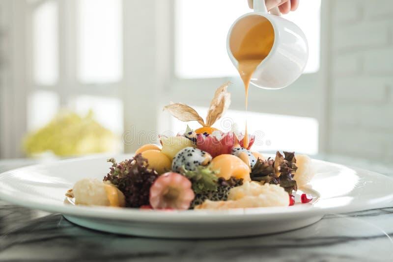 Eine Handströmende Sahnesauce in Mischfruchtsalat stockfotos