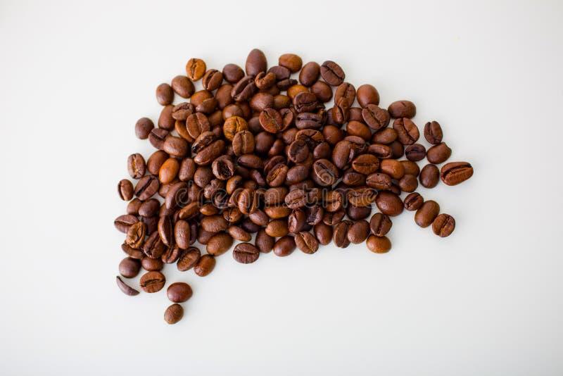 Eine Handvoll Kaffeebohnen auf einem weißen Hintergrund Draufsicht, Nahaufnahme lizenzfreie stockbilder