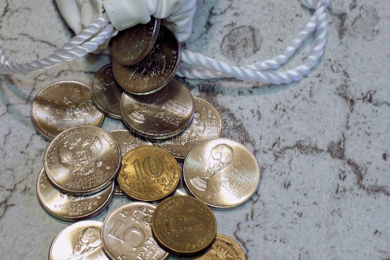 Eine Handvoll russische Jahrestagsmünzen des Eisens goss aus einer weißen Tasche, Geld heraus stockbilder