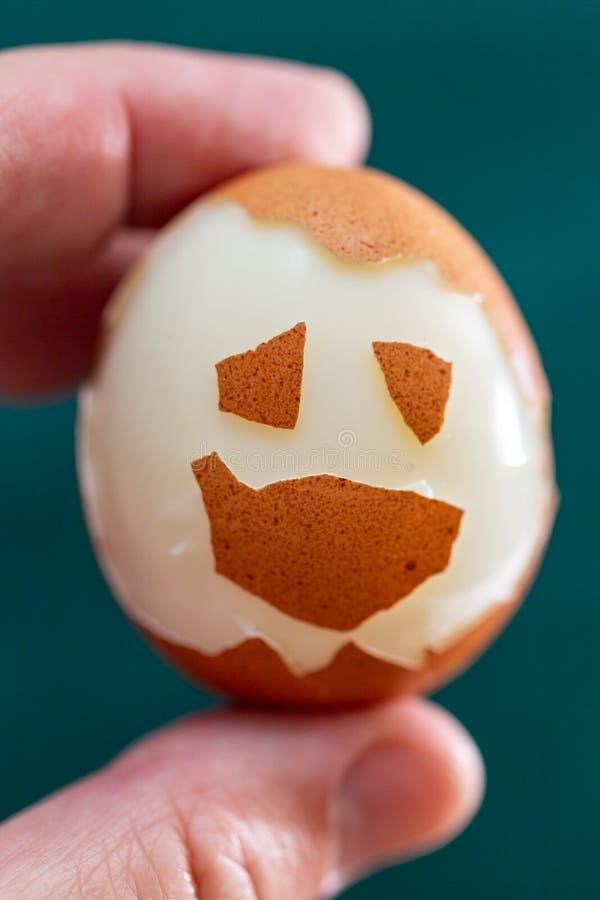 Eine hartgekochte Hühnerei in einer Hand auf einem grünen Hintergrund Lustiges Gesicht gemacht von der Eierschale auf der Oberflä lizenzfreies stockfoto