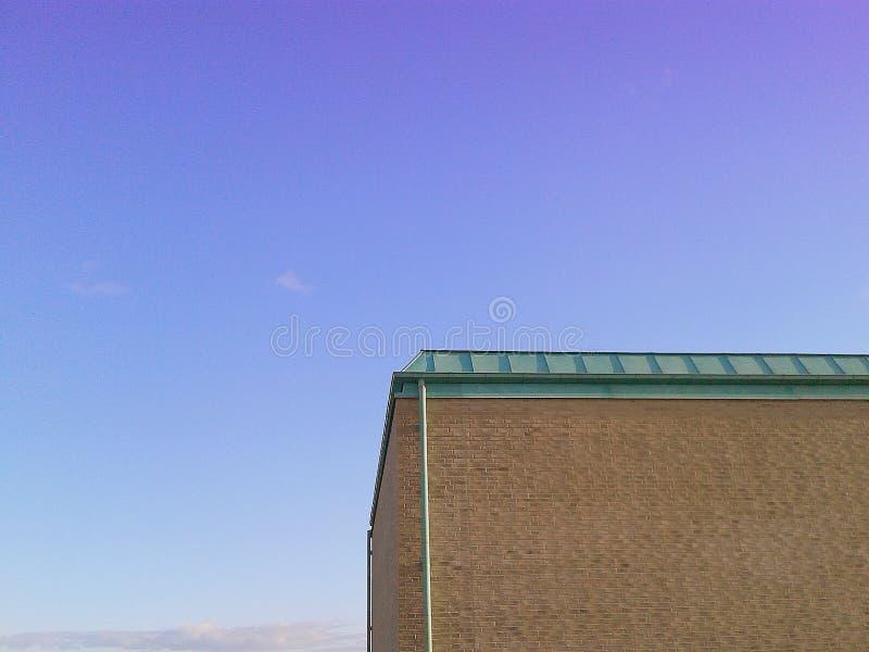 Eine Hausecke gegen einen blauen Himmel stockfotografie
