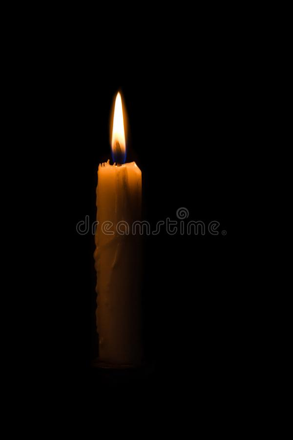 Eine helle Kerze, die hell im schwarzen Hintergrund brennt lizenzfreie stockbilder