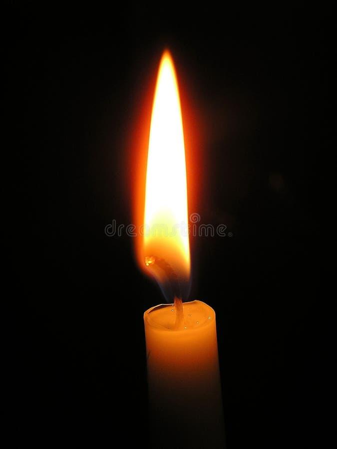 Eine helle Kerze, die hell im schwarzen Hintergrund brennt lizenzfreie stockfotografie