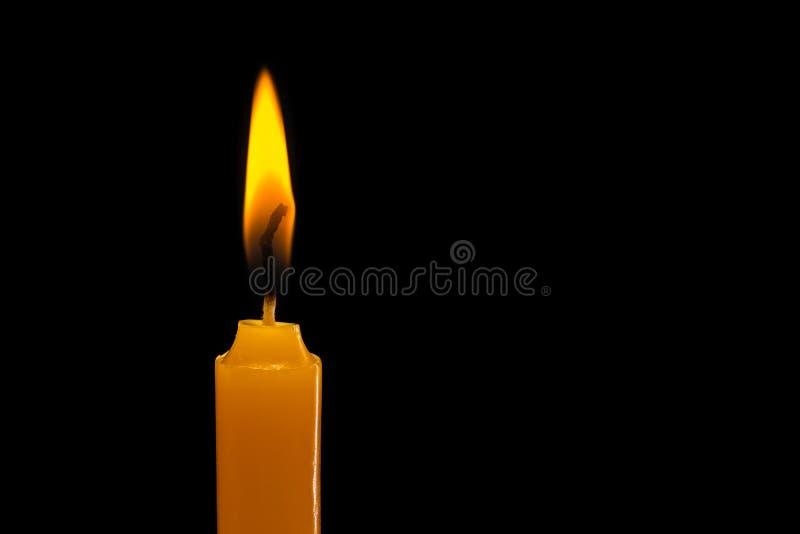 Eine helle Kerze hell brennend Atelieraufnahme lokalisiert auf Schwarzem stockbild