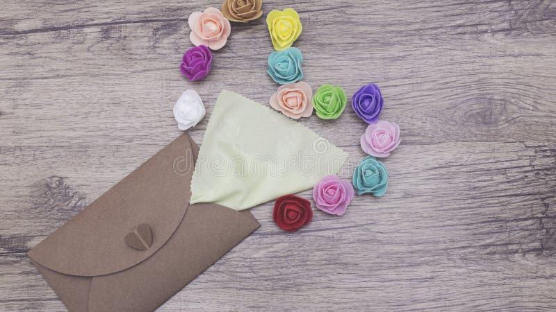Eine hellgrüne Serviette haftet aus dem Handwerksumschlag heraus In Form verziert vom Herzen mit mehrfarbigen Rosen flaches Lageb lizenzfreie stockfotos