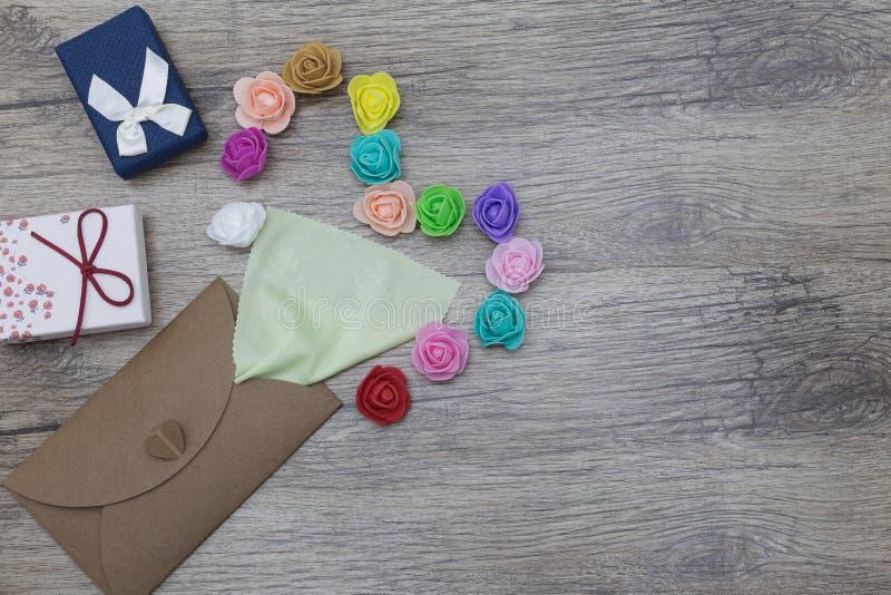 Eine hellgrüne Serviette haftet aus dem Handwerksumschlag heraus In Form verziert vom Herzen mit mehrfarbigen Rosen flaches Lageb lizenzfreie stockbilder