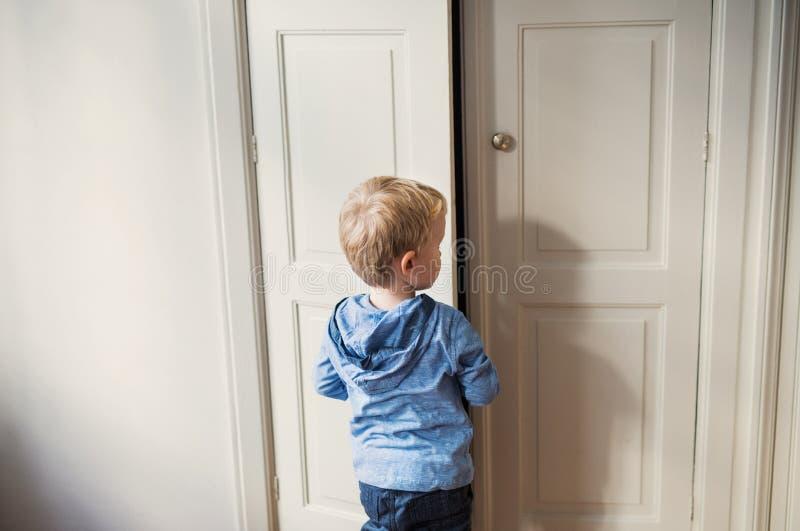 Eine hintere Ansicht der Kleinkindjungenstellung nahe Tür nach innen in einem Schlafzimmer lizenzfreie stockfotografie