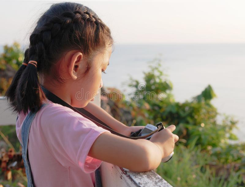 Eine Holdingkamera des kleinen Mädchens mit dem Machen eines Fotos Asiatisches Kind, das Foto in der Dämmerung mit Kopienraum mac stockbild