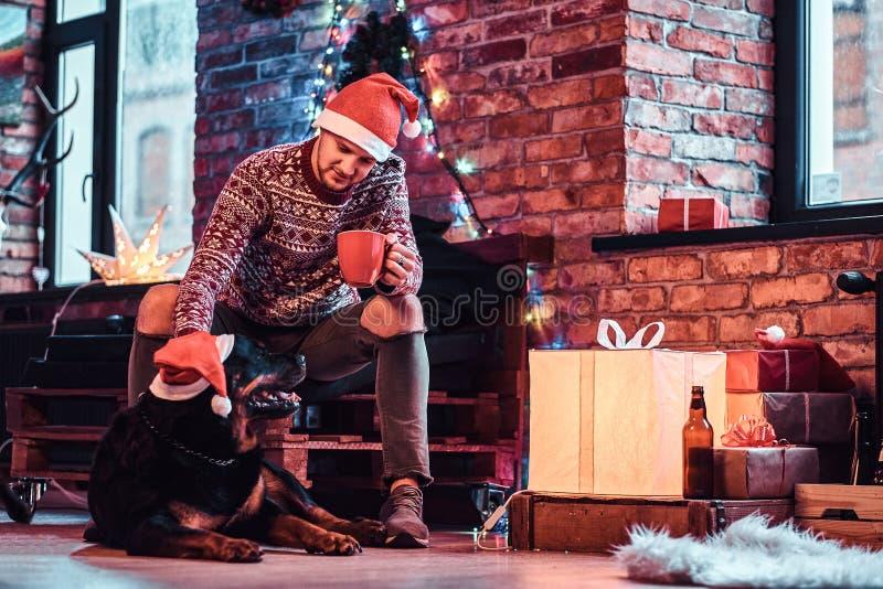 Eine Holdingschale des jungen Mannes mit Kaffee während der Weihnachtszeit mit seinem netten Hund in einem verzierten Wohnzimmer lizenzfreies stockfoto