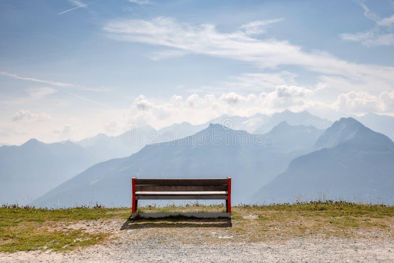 Eine Holzbank an der Spitze der Alpen, ein Platz, damit Touristen schöne Landschaften sich entspannen und betrachten lizenzfreie stockfotos