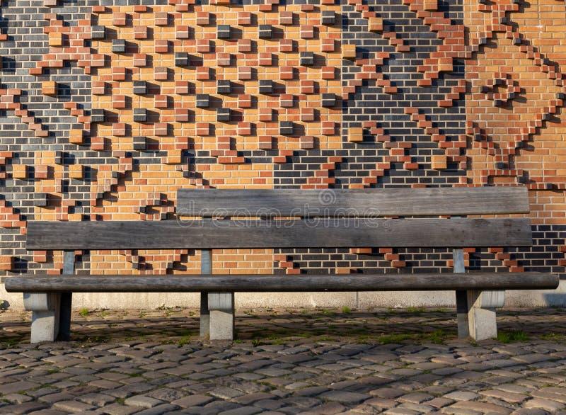 Eine Holzbank vor einer sehr kunstvollen Backsteinmauer stockfoto