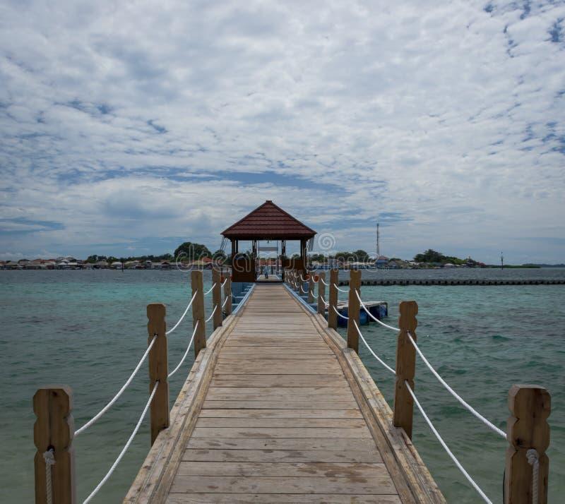 Eine Holzbrücke, die zu Gazebo mit Dorfbewohnerhaus im Hintergrund führt lizenzfreie stockfotografie