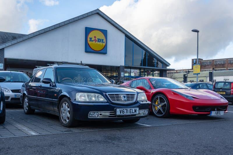 Eine Honda-Legende 3 5 v6 und Ferrari 458 neben einander geparkt im Parkplatz eines Aldi-Speichers lizenzfreies stockbild