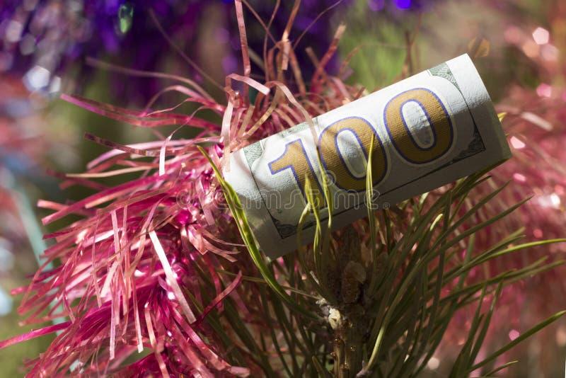 Eine Hundertdollar-Rechnung stürzte mit einem Stroh ist auf den Niederlassungen der neues Jahr ` s Fichte ein Konzept-Kosten oder stockfotografie