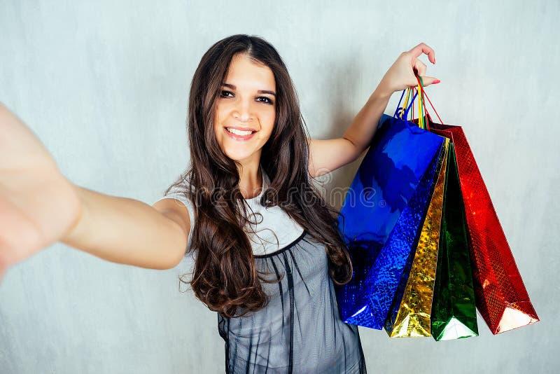 Eine indische Frau hält Einkaufstaschen in der Hand und macht sich selbst Die Idee von Verkauf, Rabatten, Einkaufen stockbild