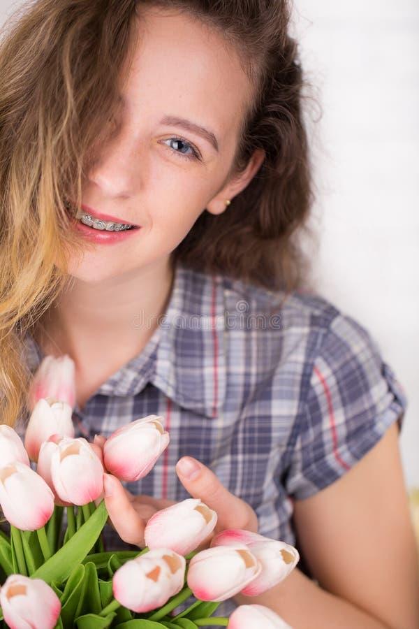 Eine Jugendliche lächelt mit Birken Aufstellung gegen einen Backsteinmauerhintergrund mit einem Blumenstrauß von Tulpen stockfoto