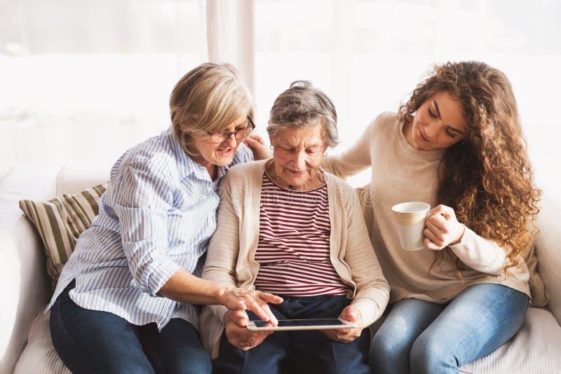 Eine Jugendliche, eine Mutter und eine Großmutter mit Tablette zu Hause stockfotografie
