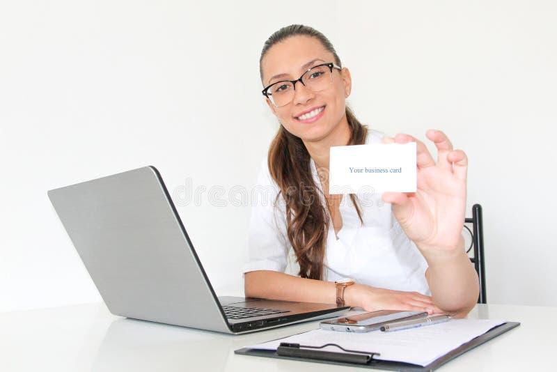 Eine junge Ärztin mit einem Laptop in ihrem Büro hält eine Visitenkarte lizenzfreies stockfoto