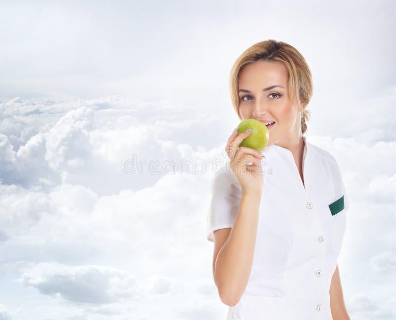 Eine junge attraktive Ärztin, die einen Apfel isst stockfoto