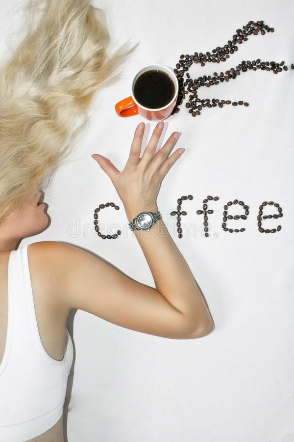 Eine junge blonde Frau mit dem langen Haar dehnt heraus ihre Hand mit einer Uhr ausdehnt über einen Tasse Kaffee, auf einem weiße lizenzfreie stockfotografie
