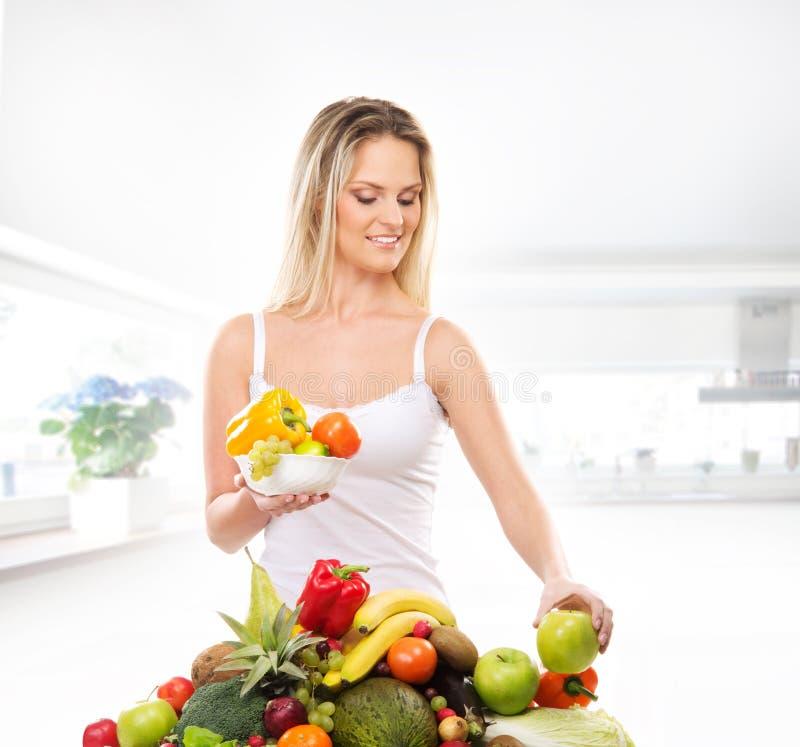 Eine junge blonde Frau mit Früchten in einer weißen Küche stockbild