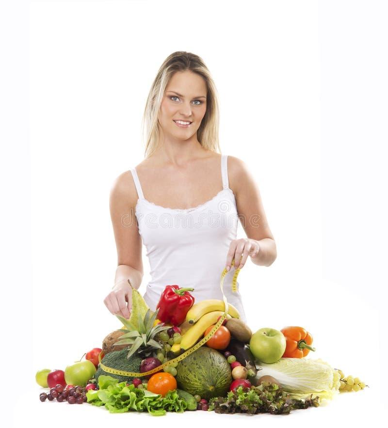 Eine junge blonde Frau und ein Stapel der frischen Früchte stockbild