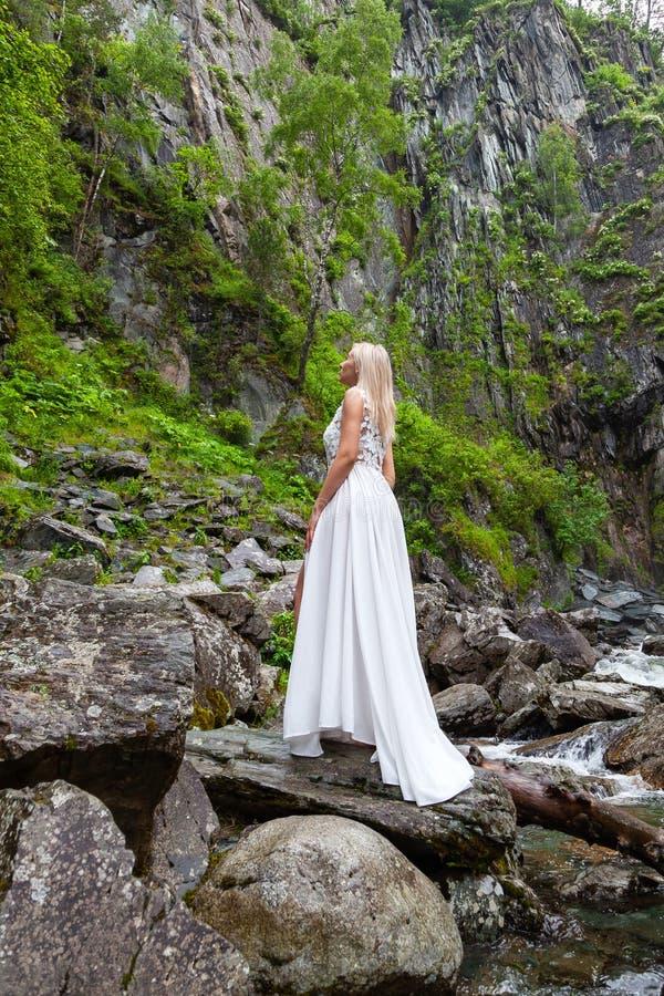 Eine junge blonde Mädchenstellung mit ihrer Rückseite in einem weißen Boudoirkleid in den Bergen gegen einen Hintergrund eines Wa stockfoto