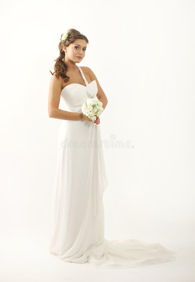 Eine junge Brunettebraut in einem schönen weißen Kleid stockbild