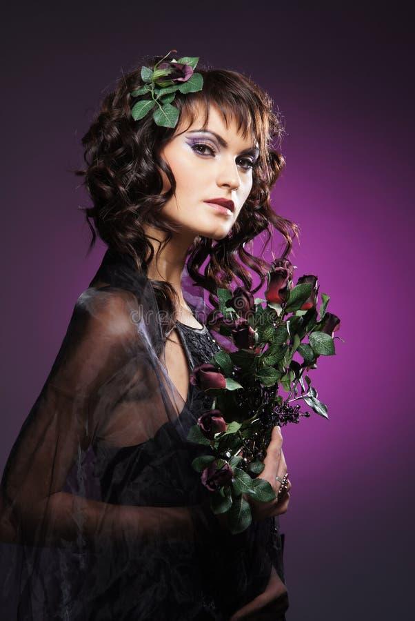 Eine junge Brunettefrau in den Blumen und in einem dunklen Kleid stockbild