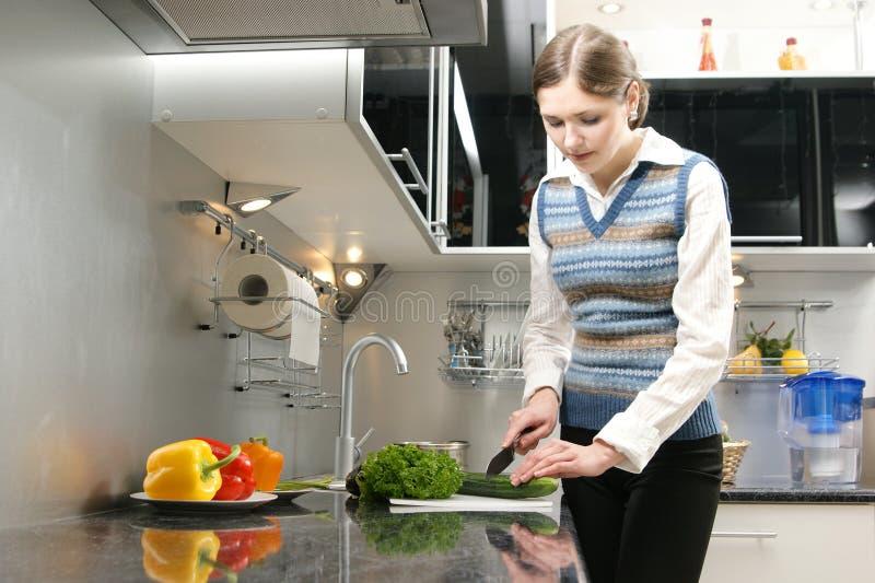 Eine junge Brunettefrau, die in der Küche arbeitet lizenzfreie stockbilder