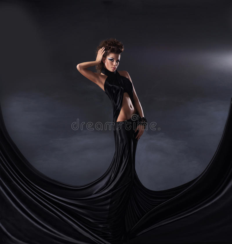 Eine junge Brunettefrau, die in einem dunklen Kleid aufwirft stockfotografie