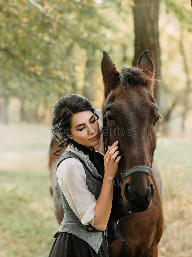 Eine junge Dame in einem Weinlesekleid, mit Weichheit und mit Neigung umarmt ihr Pferd Eine alte, gesammelte Frisur, ein leichtes lizenzfreie stockfotos