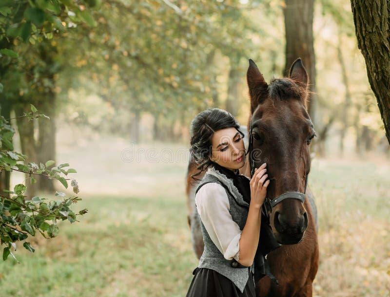 Eine junge Dame in einem Weinlesekleid schlendert durch den Wald mit ihrem Pferd Das Mädchen hat eine weiße Bluse, ein Jabot, ein stockfotos